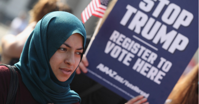 Muslim woman in front of an anti-Trump sign