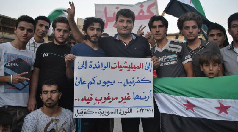 Raed Fares stands with Kafranbel residents holding banner